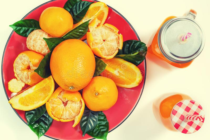 Red plate with oranges and tangerines green leaves bottle with juice on light background Top view copy space. Red plate with oranges and tangerines green leaves stock image