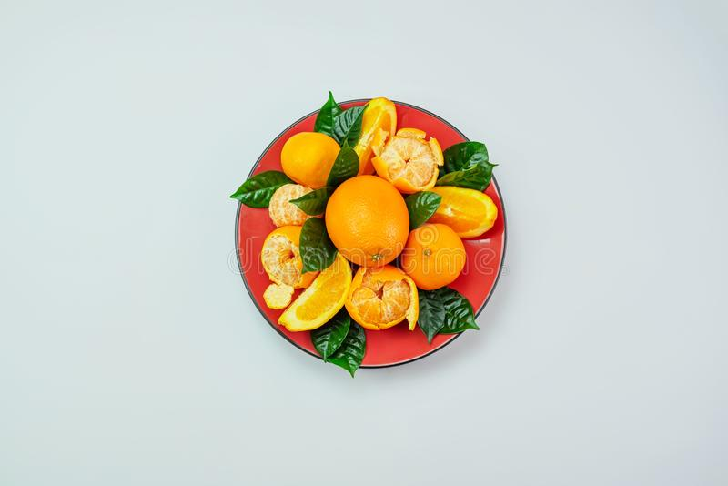 Red plate of oranges and tangerines with green leaves on a light background Top view copy space. Red plate of oranges and tangerines with green leaves on a light royalty free stock photo