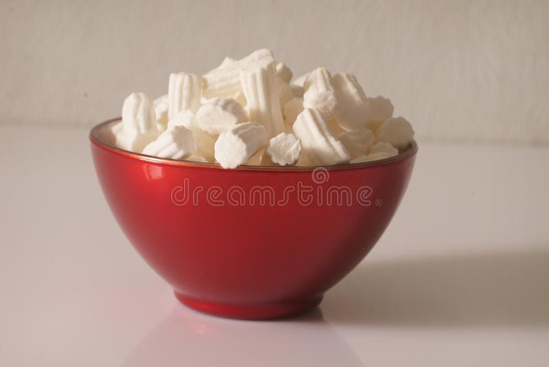 A red plate wit marshmallows on a white background. Close up. Christmas photo. royalty free illustration