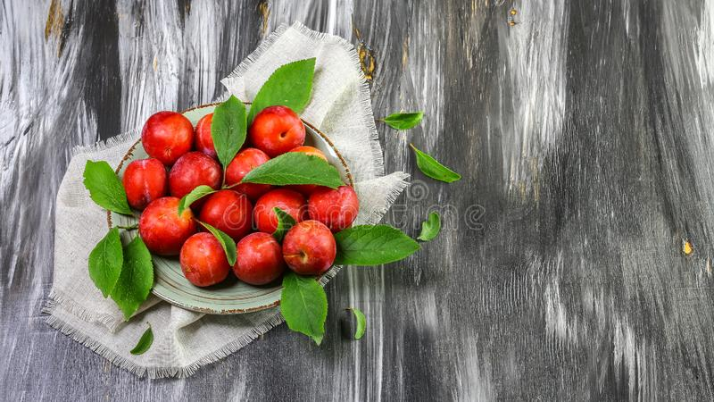 Red plums on old wooden background, Seasonal harvest crop local produce concept. Authentic lifestyle image.  royalty free stock photos