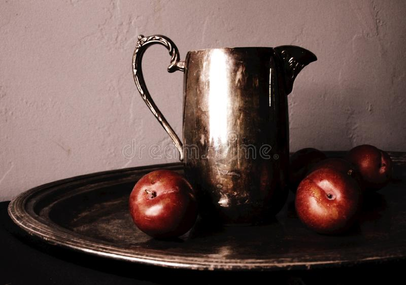Red Plums on a Tarnished Silver Tray Beside a Tarnished Silver Pitcher royalty free stock image