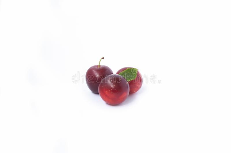 Red plums on white. Sweet three red plums isolated on white background royalty free stock images