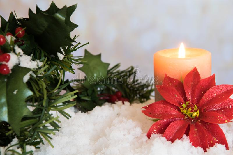 Red Poinsettia flower with lit candle and Mistletoe in snow. White Christmas Background with holiday theme stock photos