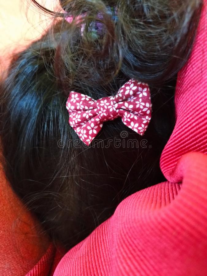 Red polka dot bow on kid`s hair. stock photo