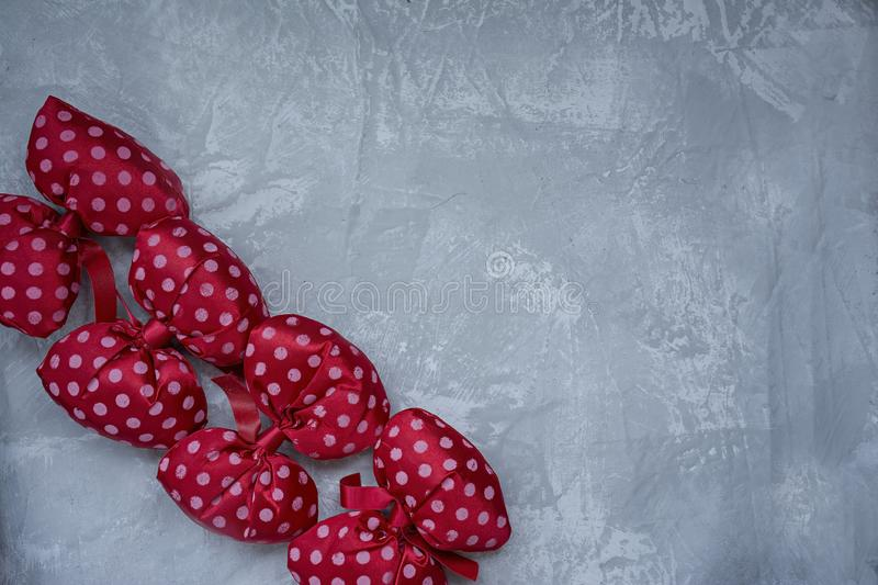 Red polka dot bows. Plush bow A toy. Light background under the concrete. Space for text stock illustration