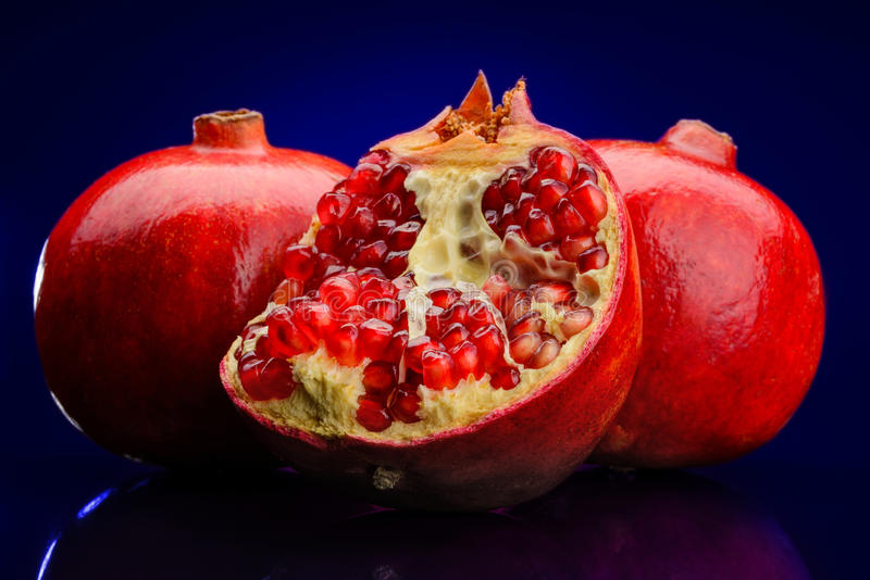 Red pomegranate on dark blue background royalty free stock photography
