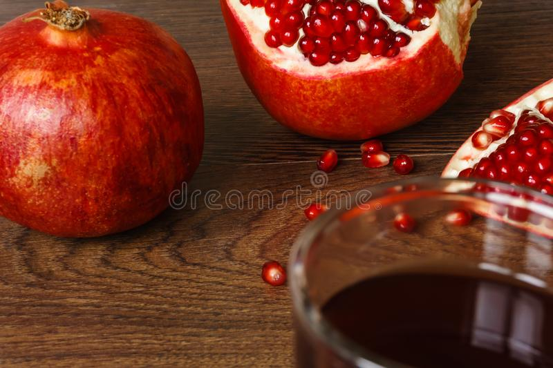 Red pomegranate fruits, seeds and glass with juice on a dark surface royalty free stock photography