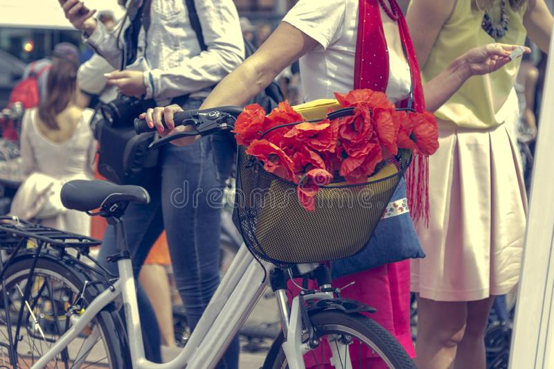 Red poppies in a bicycle basket. Woman in red skirt holds the handlebar.  royalty free stock photography