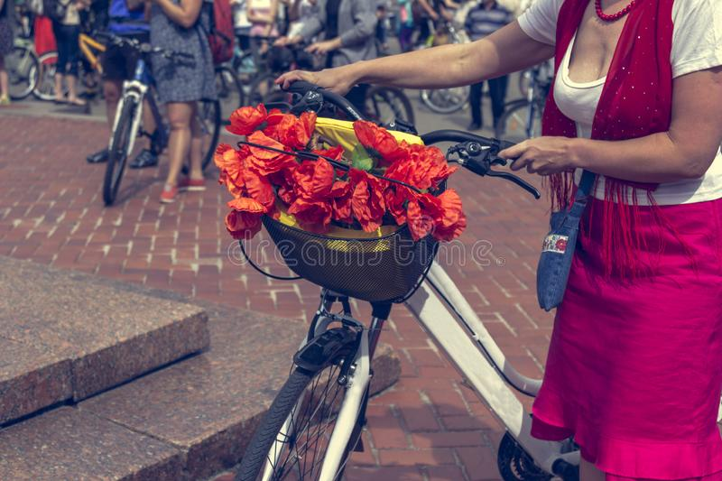 Red poppies in a bicycle basket. Woman in red skirt holds the handlebar.  stock photography