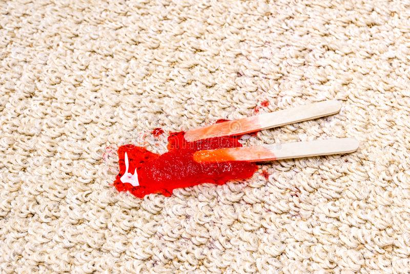 Red Popsicle melting on carpet stock photos