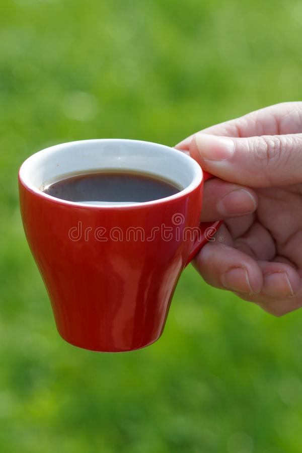 Red porcelain cup of coffee in female hand with green grass on the background stock images