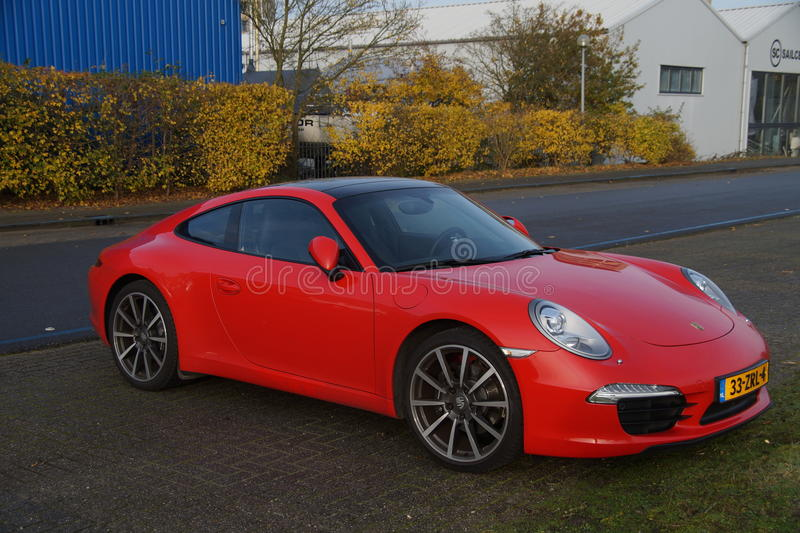 Red Porsche 911. Almere Poort, Flevoland, The Netherlands - November 14, 2014: A bright red German manufactured Porsche 911 Carrera sports car parked in a royalty free stock photography