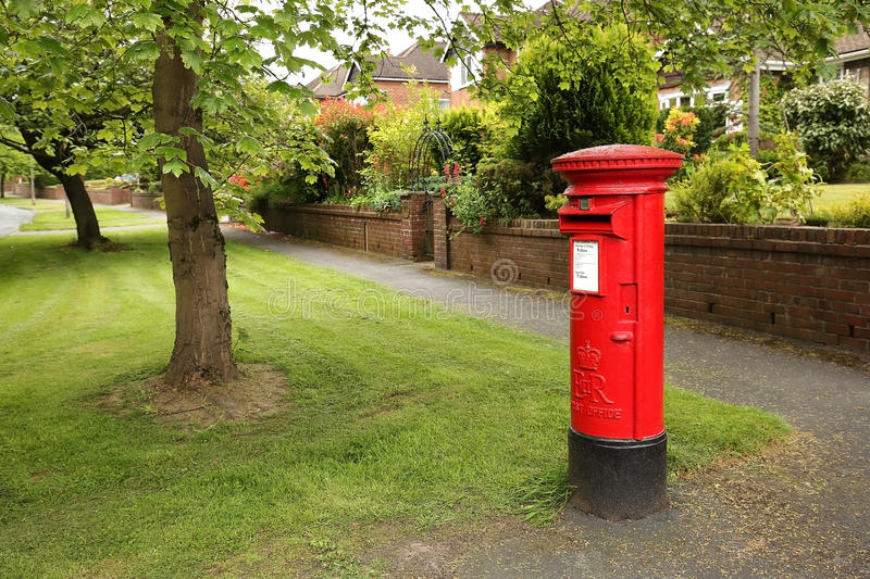 Red post box in the UK. Victorian red post box on a residential tree lined street in Wilmslow, United Kingdom stock image