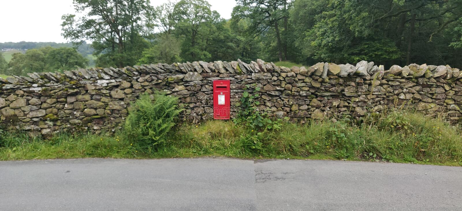 Red postbox in Drystone wall royalty free stock image