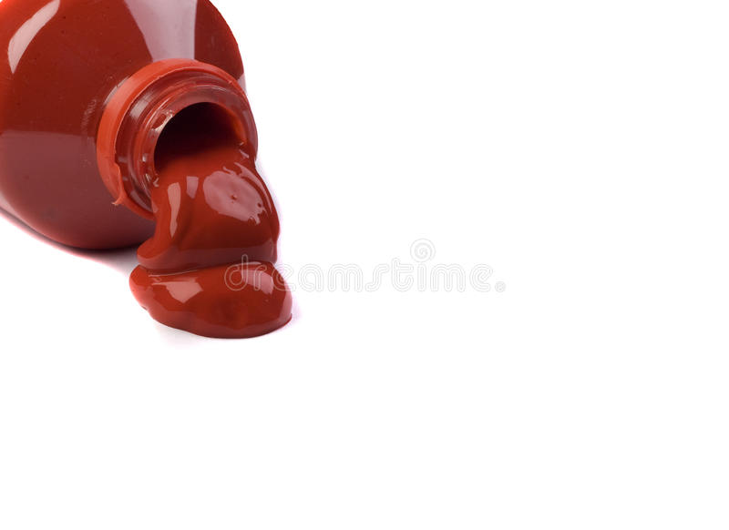 Red poster paint. A red poster paint bottle spills onto white background stock photography