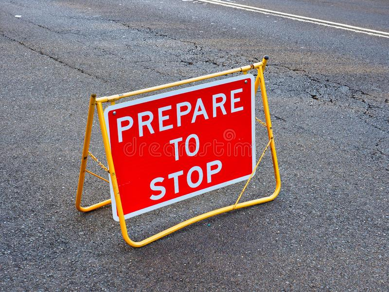 Prepare to Stop Traffic Control Sign. A red prepare to stop warning traffic control sign on worn and broken tarmac road stock images