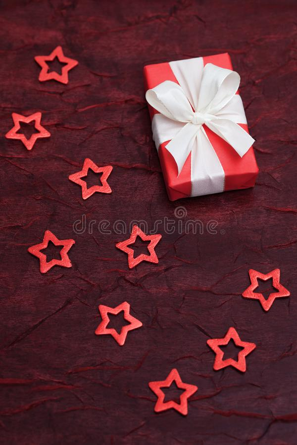 Red present with a white bow on a red shimmering cloth, surrounded by red cut out stars. royalty free stock image