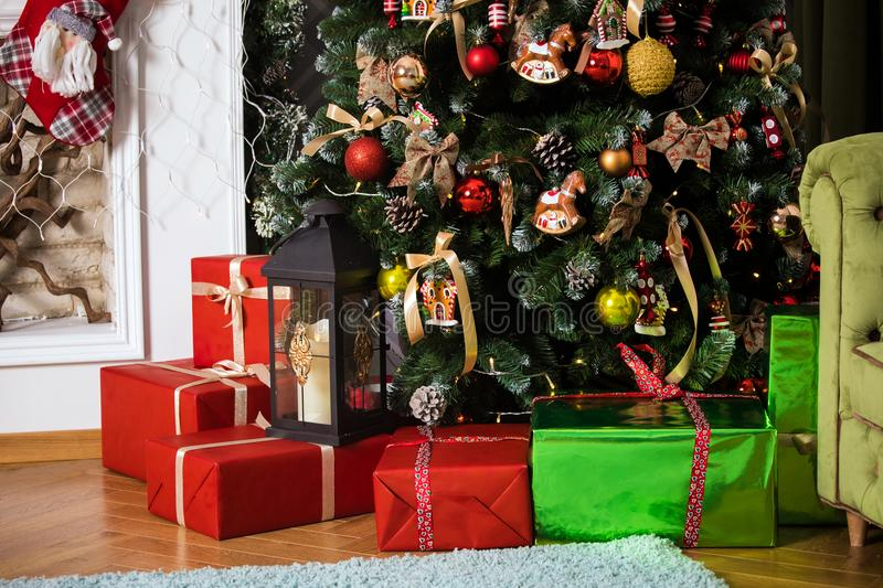Red presents boxes under decorated New Year tree royalty free stock photos