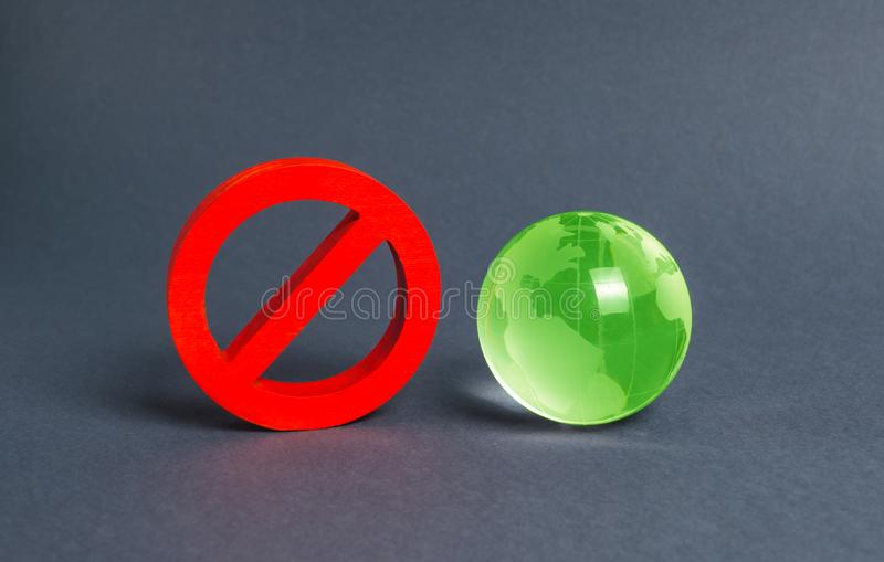 Red prohibition symbol NO and green globe planet earth glass ball. Prohibitions, obstacles and censorship, opponents. Of globalization and isolationism stock photography