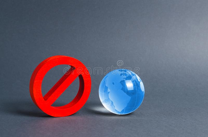 Red prohibition symbol NO and planet earth glass ball. Prohibitions, obstacles and censorship, opponents of globalization. And isolationism. Environmental stock photo