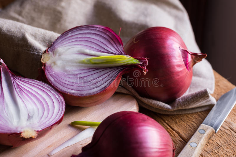 Red or purple onion cut in half, green germs, wood breadboard, linen towel, knife, kitchen table by window. Rustic style stock photos