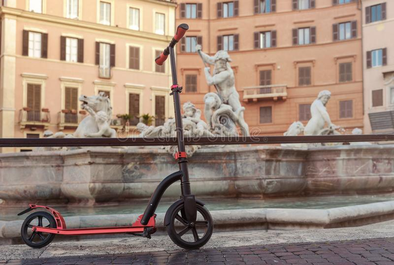 Red push scooters against the backdrop of the Fountain de Neptune on Piazza Navona in the Roma, Italy. Horizontal stock photos