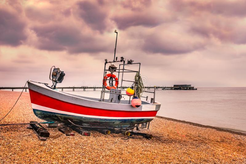 Red quaint, traditional fishing boat moored on the pebble shingle beach in Deal, Kent, UK with the pier in the background stock images
