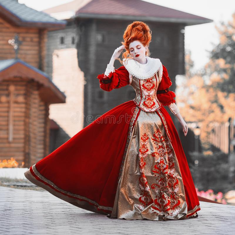 Red Queen in the castle. Red-haired woman in a chic vintage dress. Fashion Photo royalty free stock photography