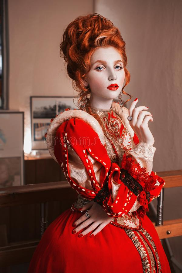Red-haired girl with blue eyes in red dress. Queen with a high hairdo. Vintage image. A woman with pale skin royalty free stock images