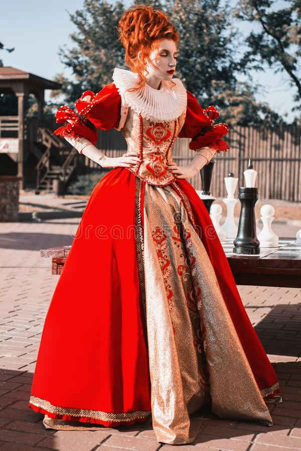 Red Queen in the castle. Red-haired woman in a chic vintage dress stock photography