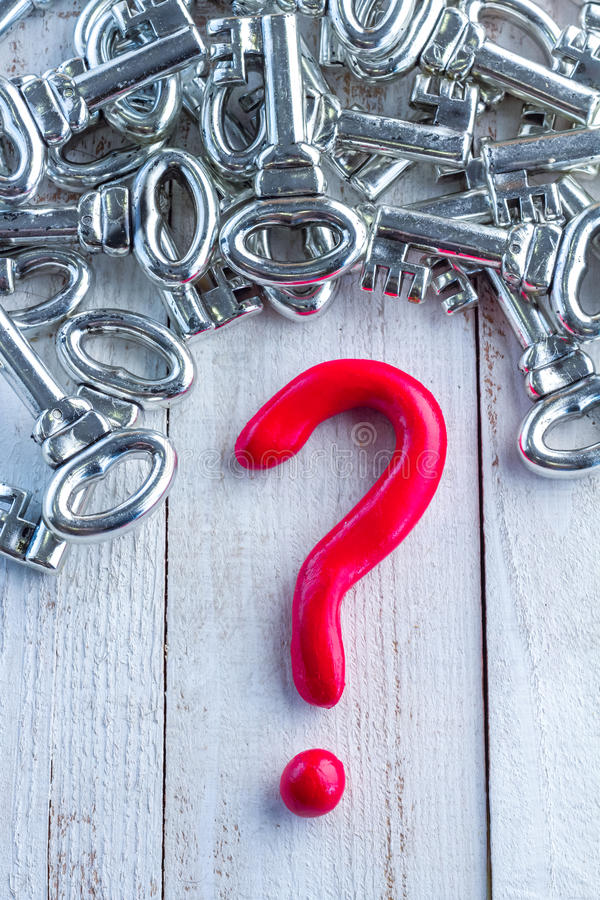 Red question mark and silver keys on white wooden table. Red question mark and silver keys on wooden table business solution concept stock image