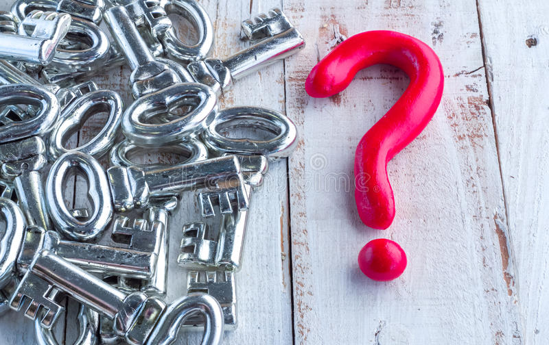 Red question mark and silver keys on wooden table. Red question mark and silver keys Could be used for the concept of keys to learning stock photos