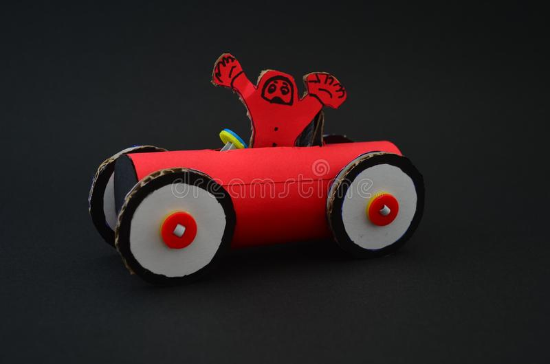 Red race car made of cardboard and paper. Red race car made of cardboard and paper in a black background royalty free stock image