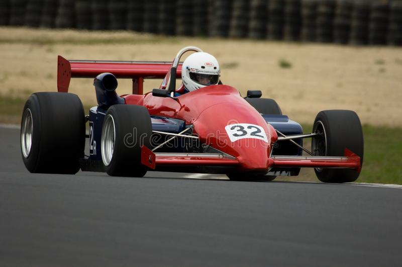 Red racing car. A Ralt RT4 historic racing car at speed on a race track. Shot at historic motorsport race meeting, classic car racing royalty free stock images
