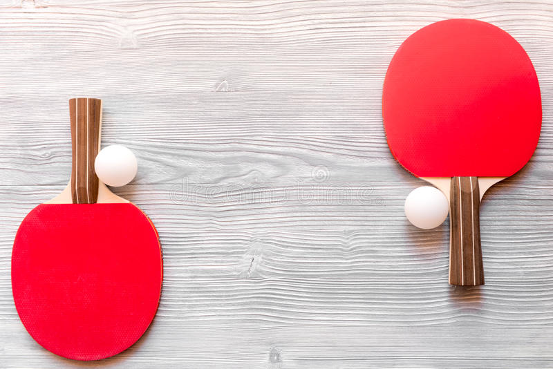 Red racket for ping pong ball wooden background top view. Red racket for ping pong ball on gray wooden background top view royalty free stock image