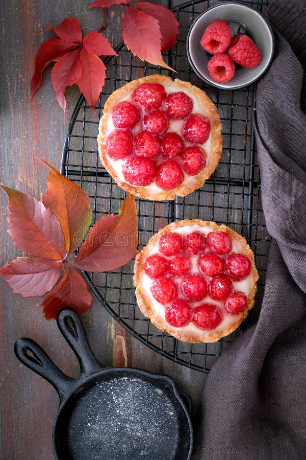 Red raspberry shortbread tarts with vanille custard and glazed fresh raspberries on cooling rack over dark brown stock image