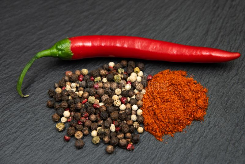 Red raw chili pepper, chili ground powder and mised peppercorns. On dark background.  royalty free stock images