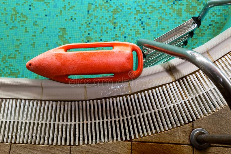 Red rescue buoy near the stairs in the swimming pool.  stock photo
