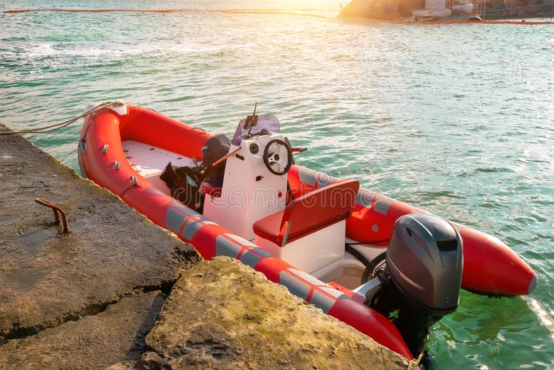Red rescue inflatable boat moored to the sea pier, closeup. Empty marine rescue boat royalty free stock photo