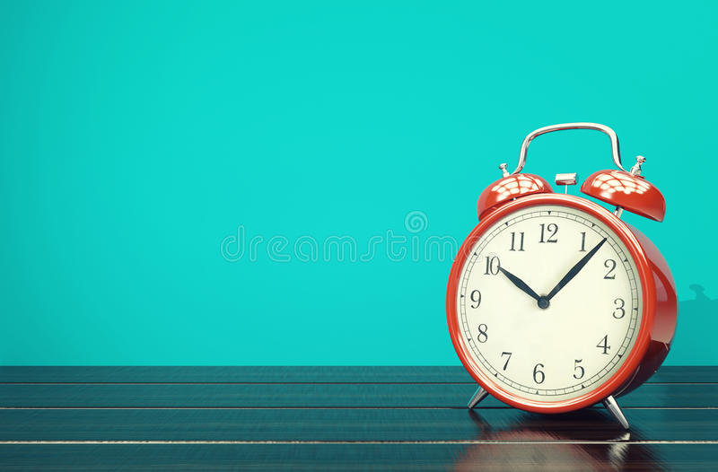 Red retro alarm clock on blue background with space stock photography