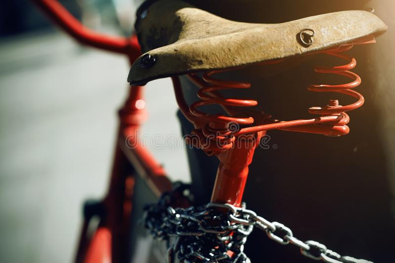 A red retro bike is tied with a metal chain to a pole royalty free stock images