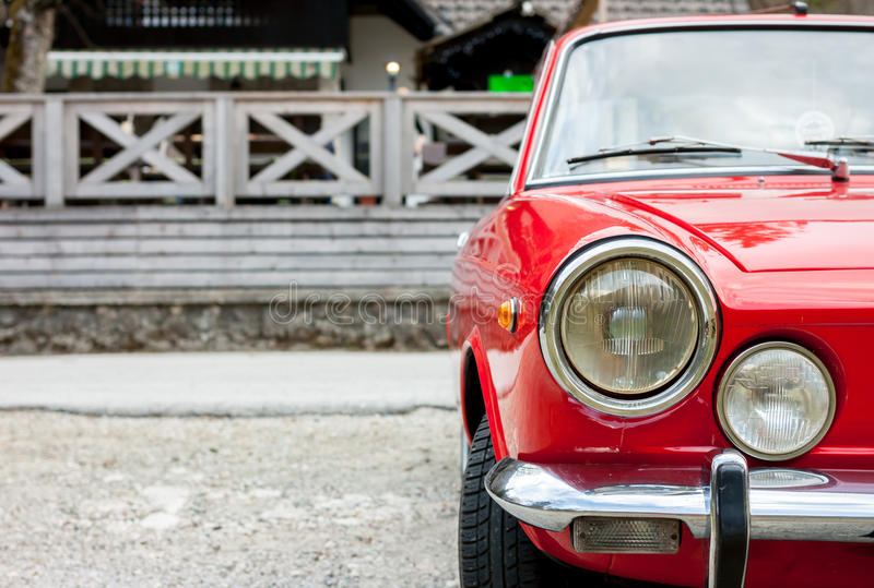 Red retro car in the countryside. Beautiful red retro sport car in the spring countryside royalty free stock image