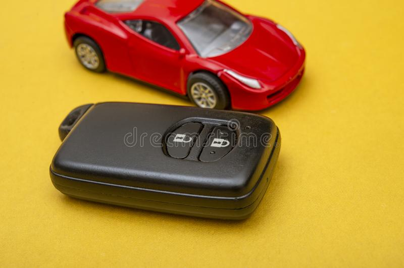 Red retro car with Car remote on yellow background, transportation concept.  royalty free stock images