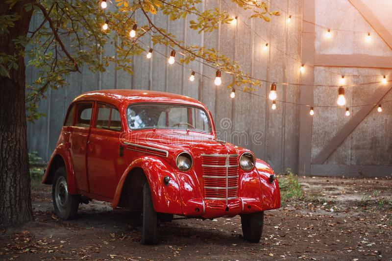Red retro car standing in the garden in the summer on a background of gray wall and burning bulbs. Vintage vehicle near the garage. Decorated with lights stock image