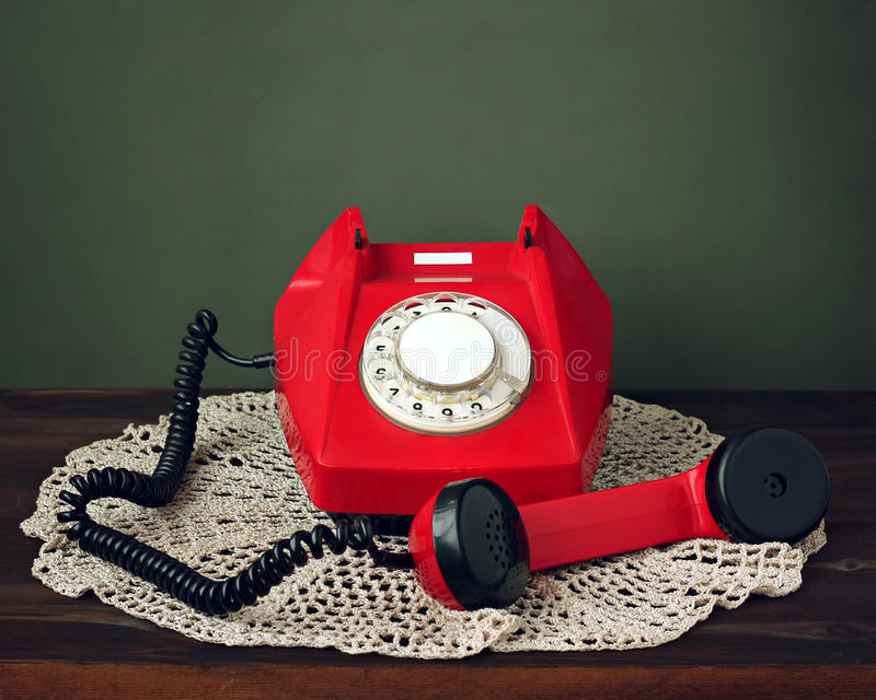 Red retro rotary phone on a lacy napkin. royalty free stock images