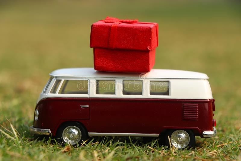 Red retro toy car with gift box. Flowers, gifts delivery concept. stock images