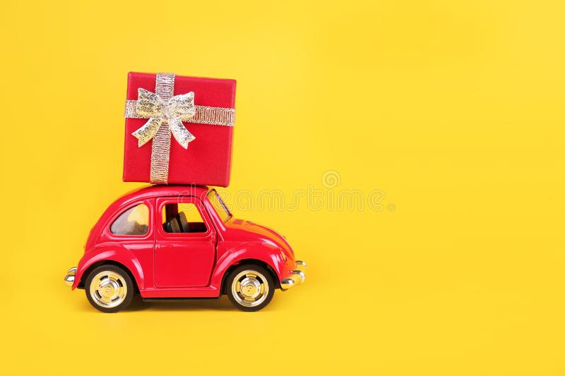 Red retro toy car with gift boxes on yellow background. Flowers, gifts  delivery concept. stock images