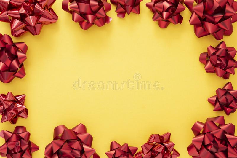 Red ribbon bows over colorful yellow background. Birthday, Christmas or Valentine's day mock up frame or border stock image