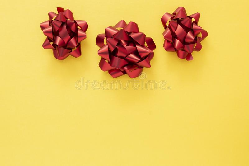 Red ribbon bows over colorful yellow background. Birthday, Christmas or Valentine's day mock up frame or border stock photos