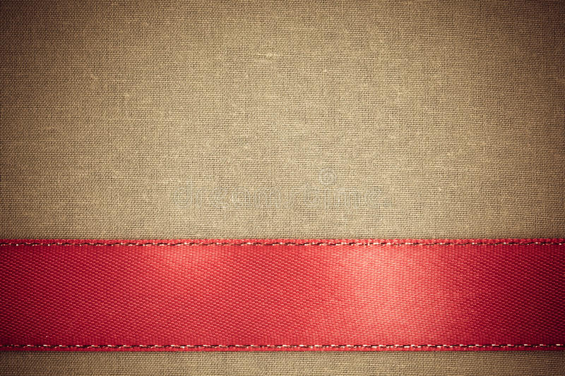 Red Ribbon On Brown Fabric Background With Copy Space. Stock Photo ...